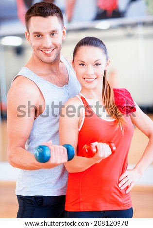 fitness, sport, training, gym and lifestyle concept - two smiling people working out with dumbbells in the gym - stock photo