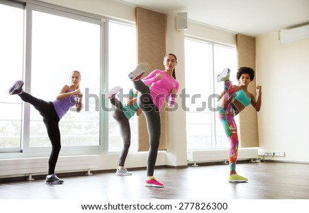 fitness, sport, training, gym and martial arts concept - group of women working out fighting technique in gym - stock photo