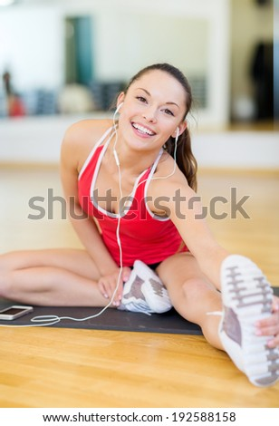 fitness, sport, training, gym, technology and lifestyle concept - smiling teenage girl with smartphone and earphones in gym