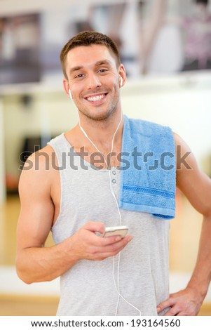 fitness, sport, training, gym, technology and lifestyle concept - young man with smartphone and towel in gym - stock photo