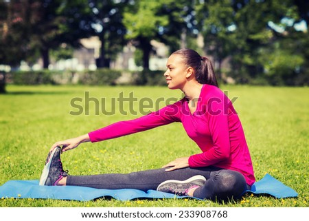 fitness, sport, training, park and lifestyle concept - smiling woman stretching leg on mat outdoors - stock photo