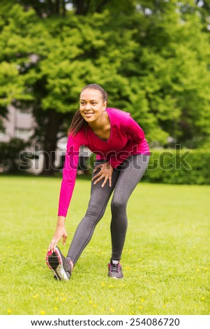 fitness, sport, training, park and lifestyle concept - smiling woman stretching leg outdoors - stock photo