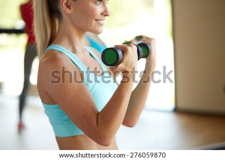 fitness, sport, training, people and lifestyle concept - closeup of woman with dumbbells flexing muscles in gym