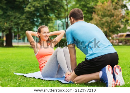 fitness, sport, training, teamwork and lifestyle concept - smiling woman with personal trainer doing exercises on mat outdoors - stock photo