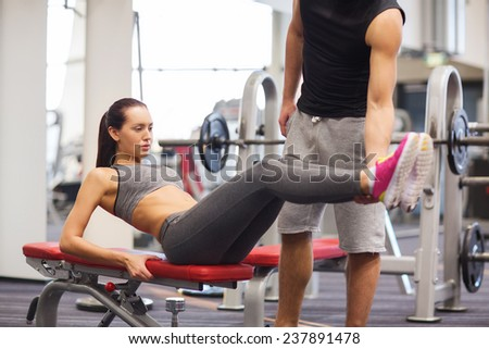 fitness, sport, training, teamwork and lifestyle concept - woman with personal trainer doing abdominal exercise in gym - stock photo