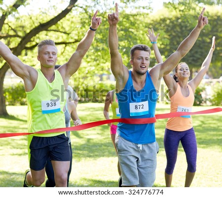 fitness, sport, victory, success and healthy lifestyle concept - happy man winning race and coming first to finish red ribbon over group of sportsmen running marathon with badge numbers outdoors - stock photo