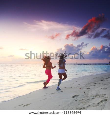 Fitness sport women running on beach at sunset - stock photo