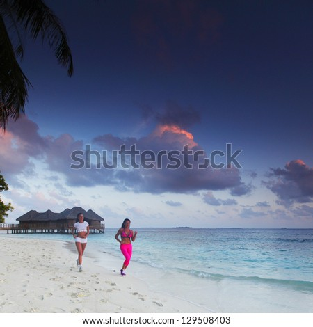 Fitness sport women running on beach at sunset