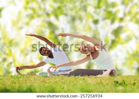 fitness, sport, yoga and people concept - happy couple stretching on mats over green tree leaves background - stock photo