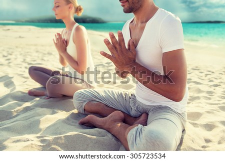 fitness, sport, yoga, people and lifestyle concept - happy couple sitting in lotus pose on beach - stock photo