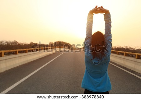 fitness sports woman runner stretching on sunrise city road - stock photo