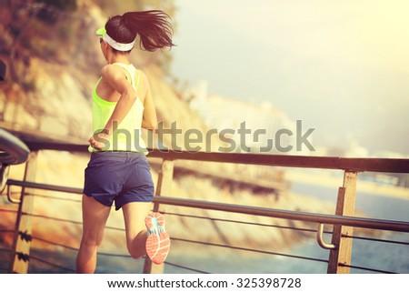 fitness sports woman running on wooden boardwalk seaside - stock photo