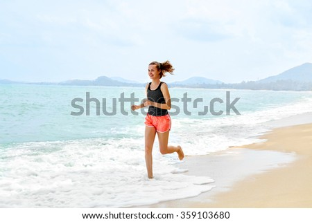 Fitness. Sporty Young Female Runner Running On Beach. Athletic Fit Woman Jogging During Workout Outside. Sports, Exercising, Healthy Lifestyle. Health Concept