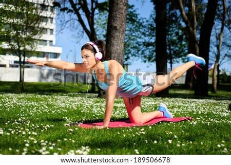 Fitness spring or summer workout outdoor. Fit woman working out and doing stretching exercises in city park. - stock photo