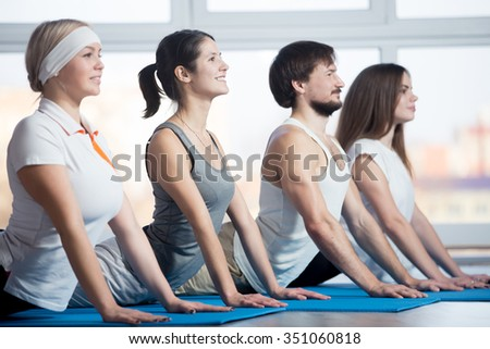 Fitness, stretching practice, group of four attractive smiling fit young people working out in sports club, doing Cobra posture, backbend exercise on blue mats in class - stock photo