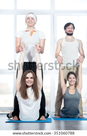 Fitness, stretching practice, group of four beautiful happy fit young people working out in sports club, doing backbend exercise on blue mats, partners helping to deepen pose, full length - stock photo