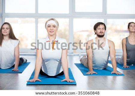 Fitness, stretching practice, group of four beautiful happy fit young people working out in sports club, doing Cobra posture, backbend exercise on blue mats in class - stock photo
