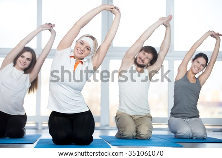 Fitness, stretching practice, group of four beautiful happy fit young people working out in sports club, doing side bend exercises with raised arms on blue mats in class - stock photo