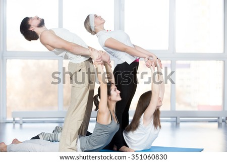 Fitness, stretching practice, group of four beautiful smiling cheerful fit young people working out in sports club, doing backbend exercise on blue mats, partners helping to deepen pose