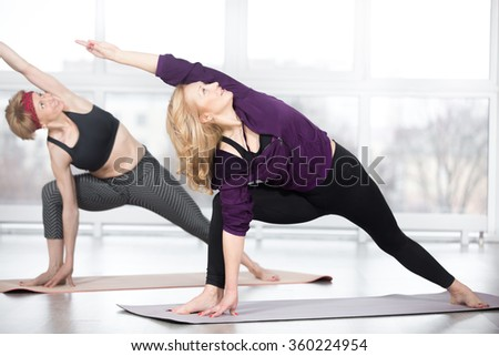 Fitness, stretching practice, group of two attractive happy smiling fit mature women working out in sports club, doing Extended Side Angle posture, utthita parshvakonasana pose in class, full length - stock photo