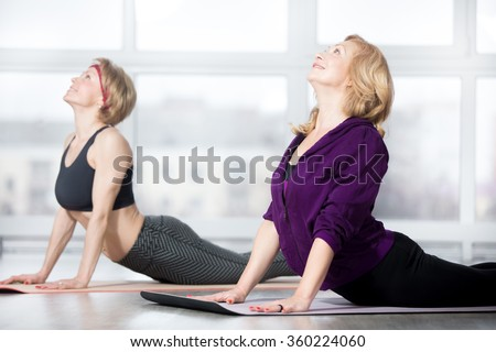 Fitness, stretching practice, group of two attractive smiling fit mature women in sportswear working out in sports club, doing Cobra posture, backbend exercise, bhudjangasana (Bhujangasana) in class - stock photo