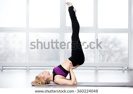 Fitness, stretching workout, attractive mature woman in violet sportswear working out in sports club, keeping fit, doing shoulderstand exercise, Viparita Karani, Upside-Down Seal pose in class - stock photo
