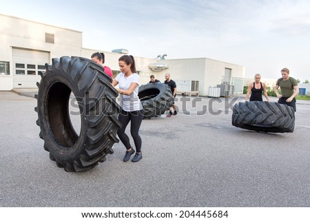 Fitness team flipping heavy tires as workout - stock photo