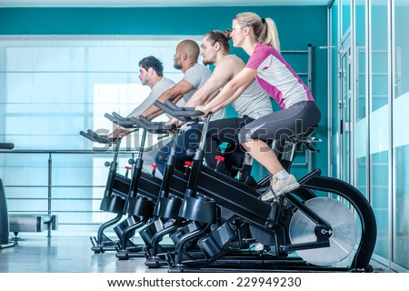Fitness together on bicycles. Four friends pedal on a stationary bike at the gym - stock photo
