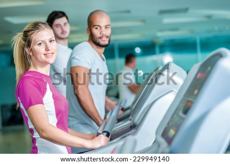 Fitness together on cross trainers. girl running on the CROSS TRAINERS and looking into the camera. - stock photo