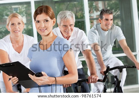 Fitness trainer coaching exercise class with seniors in gym - stock photo