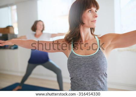 Fitness trainer doing the warrior pose during yoga class. Yoga teacher performing Virabhadrasana position in gym with people n background. - stock photo