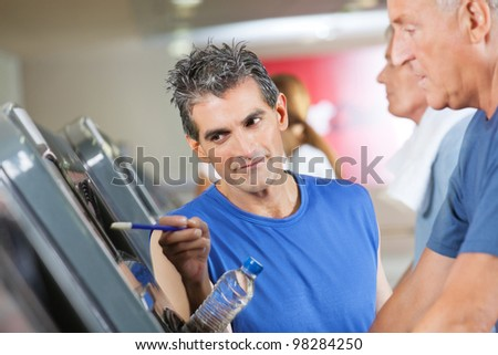 Fitness trainer explaining treadmill to senior man in gym - stock photo