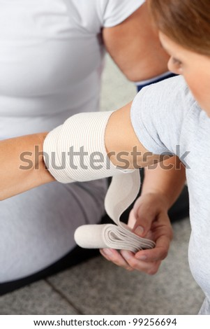 Fitness trainer fixing arm joint of woman with bandage - stock photo