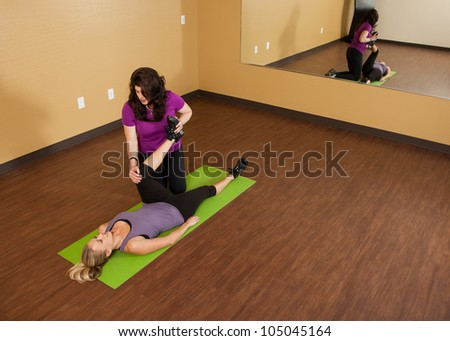 Fitness Trainer Helping Young Woman Stretch - stock photo