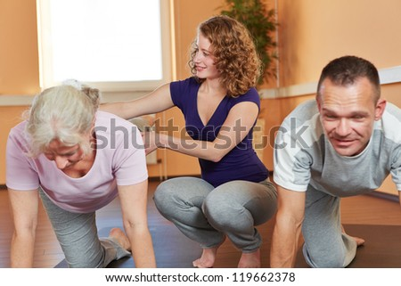Fitness trainer with senior sports group giving instructions to elderly woman - stock photo