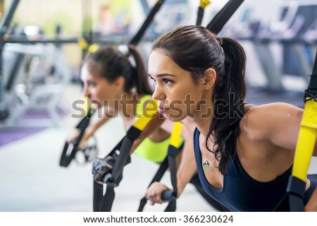 Fitness trx suspension straps training exercises women doing push-ups, working with own weith at gym - stock photo