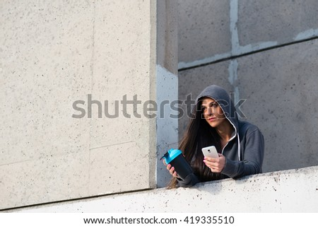 Fitness urban woman taking a workout rest for drinking protein shake and texting on smartphone. Female motivated athlete holding gym protein shaker cup. - stock photo