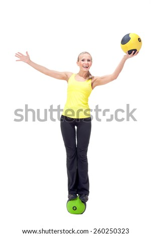 Fitness with medicine ball: beautiful elegant young woman doing exercises with a ball. Yellow and black colors