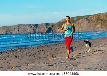 Fitness woman and dog on running workout at the beach. Sporty female runner training on summer sunset. - stock photo