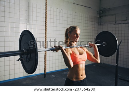 Fitness woman concentrating while lifting barbells. Strong woman lifting weights in crossfit gym. Caucasian female model with muscular body. - stock photo