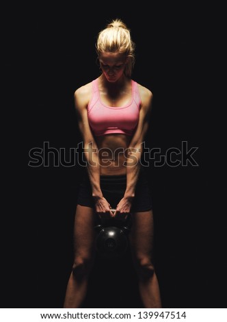 Fitness woman doing a weight training by lifting a heavy kettlebell - stock photo
