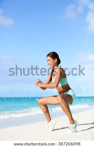 Fitness woman doing bodyweight workout training calves with plie squat calf raise exercise. Asian sport girl doing a ballet inspired ballerina pose to activate glutes and lower body by raising heels. - stock photo