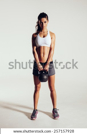 Fitness woman doing crossfit exercising with kettle bell. Beautiful fitness instructor on grey background. Female model with muscular fit and slim body. - stock photo
