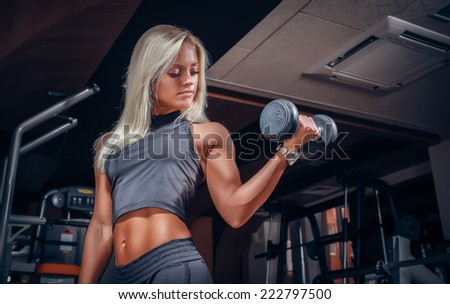fitness woman doing exercises with dumbbell in the gym - stock photo