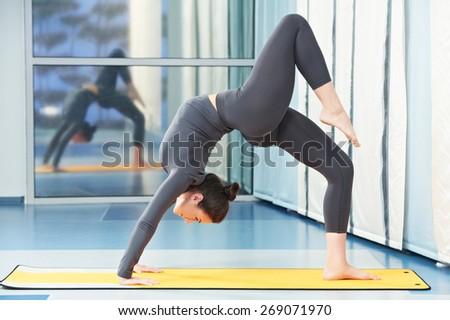 fitness woman doing gymnastic physical training exercise in gym - stock photo