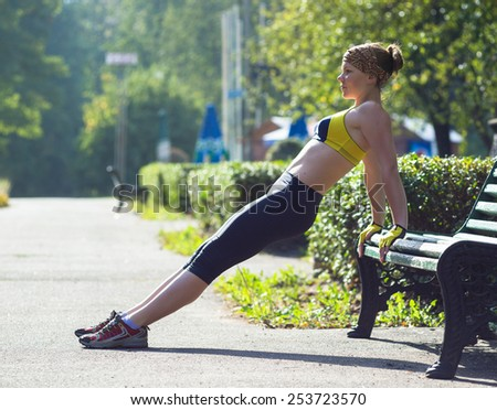 Fitness woman doing push-ups during outdoor cross training workout. Beautiful young and fit fitness sport model training outside.  - stock photo