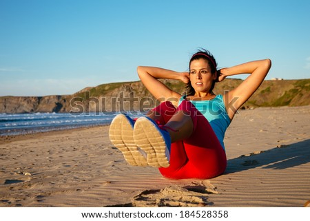 Fitness woman doing sit ups exercising on beach. Sporty girl workout outdoors on summer. - stock photo