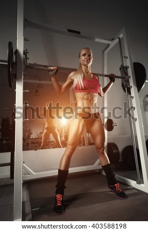 Fitness woman doing squats with the barbell at the gym. Smith Machine in the gym.  Fitness woman in the gym. Perfect female figure