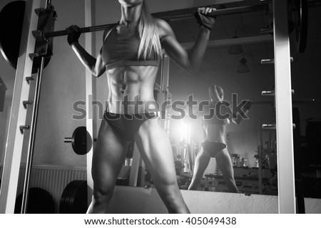 Fitness woman doing squats with the barbell at the gym. Smith Machine in the gym.  Fitness woman in the gym. Perfect fitness female figure. Fitness - concept of healthy lifestyle. Crossfit woman - stock photo