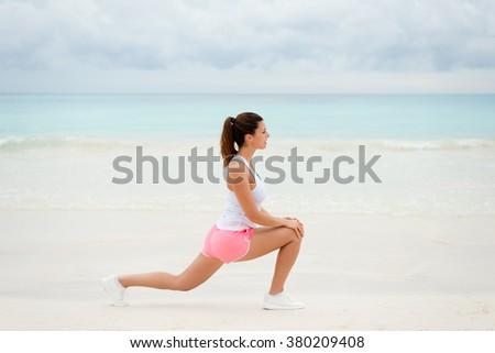 Fitness woman doing stretching legs exercise for warming up before running at the beach. Healthy exercising on summer. - stock photo